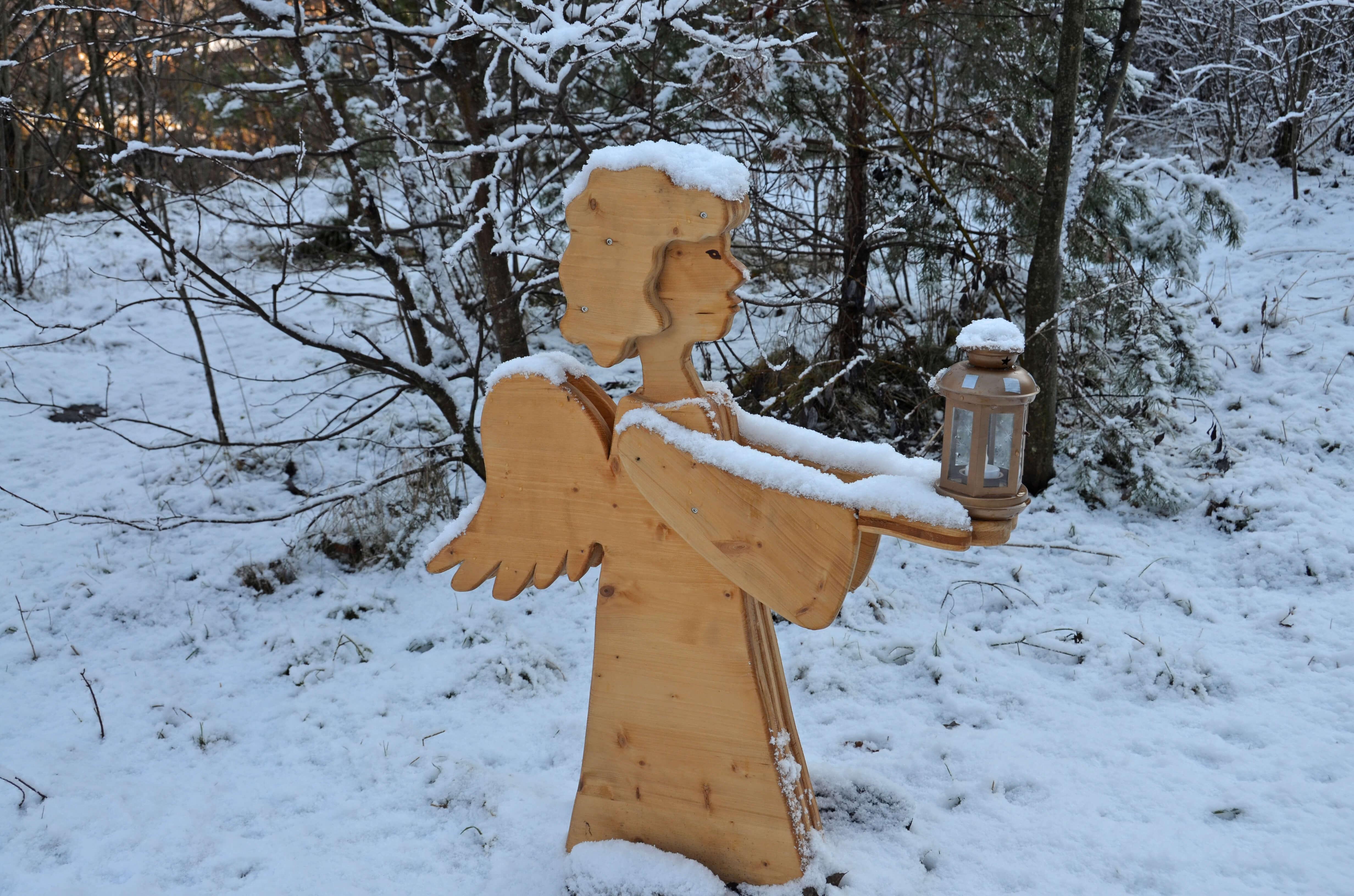 Der Engel aus Holz beleuchtet den Weg mit seiner Laterne