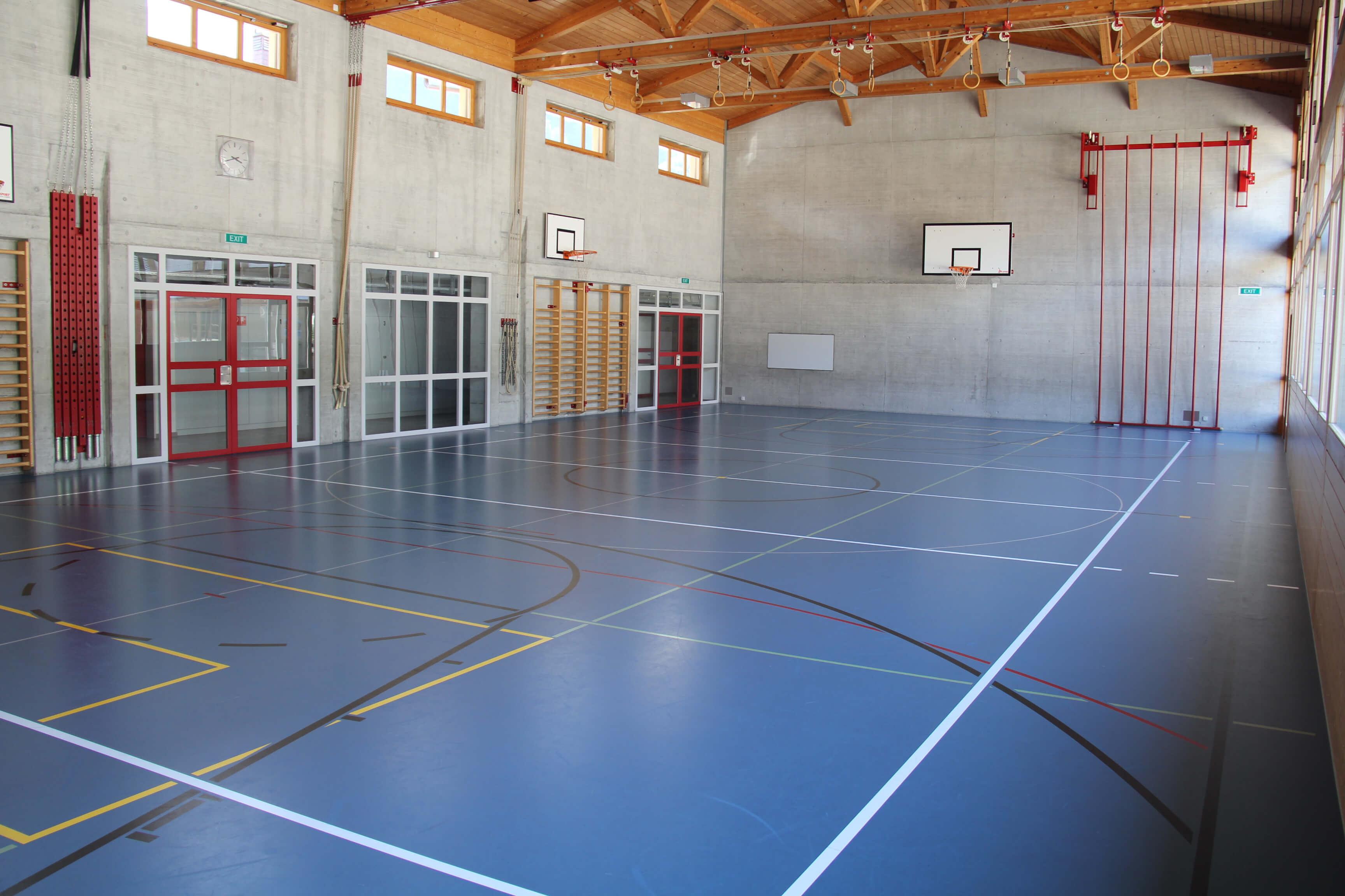 Grosse Turnhalle mit Kletterstange und Basketball-Körben