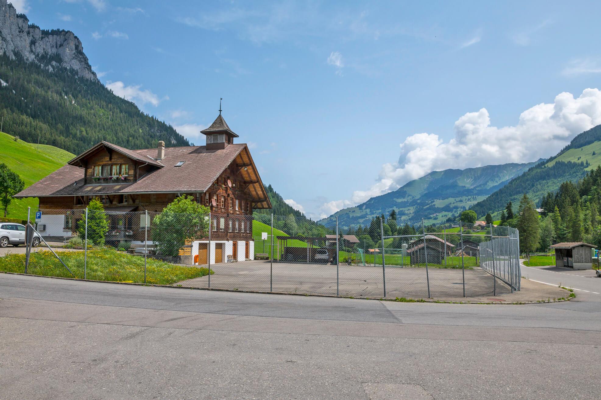 Schulhaus Zwischenflüh mit Park- und Sportplatz