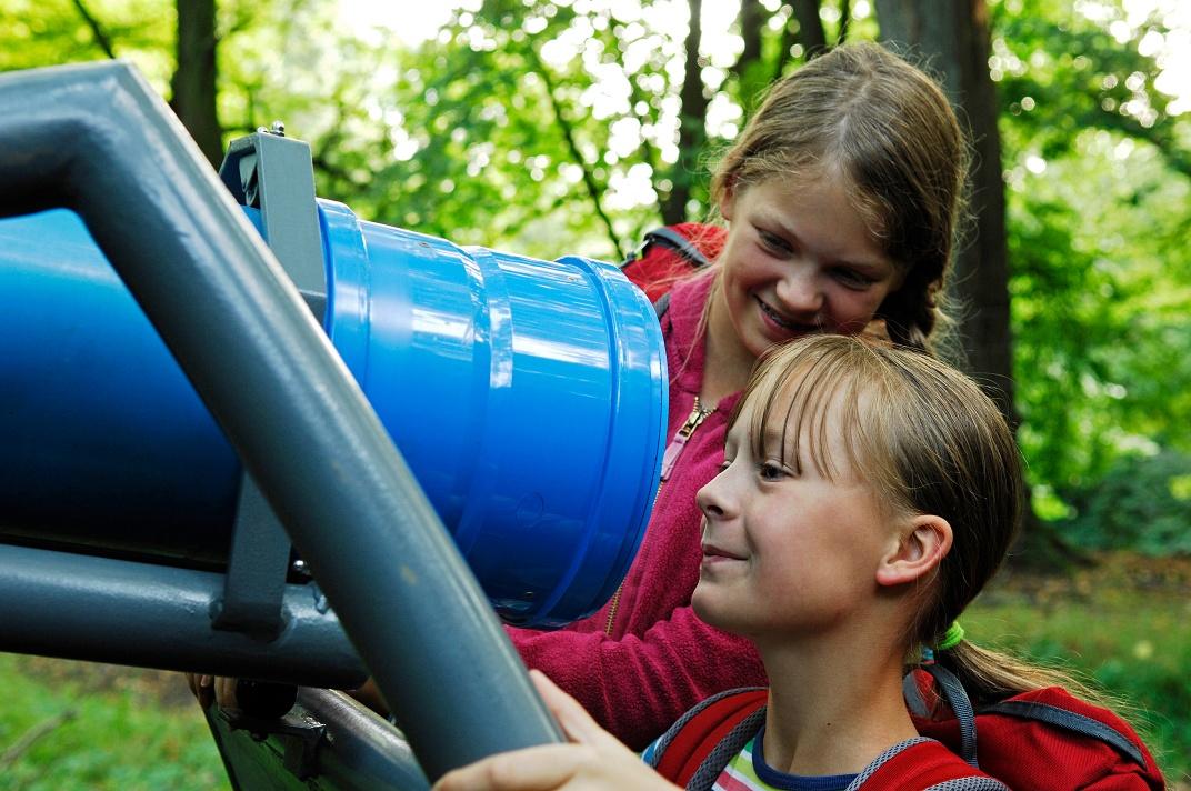 Mädchen schauen in das Wippenkaleidoskop auf dem Rosenberg