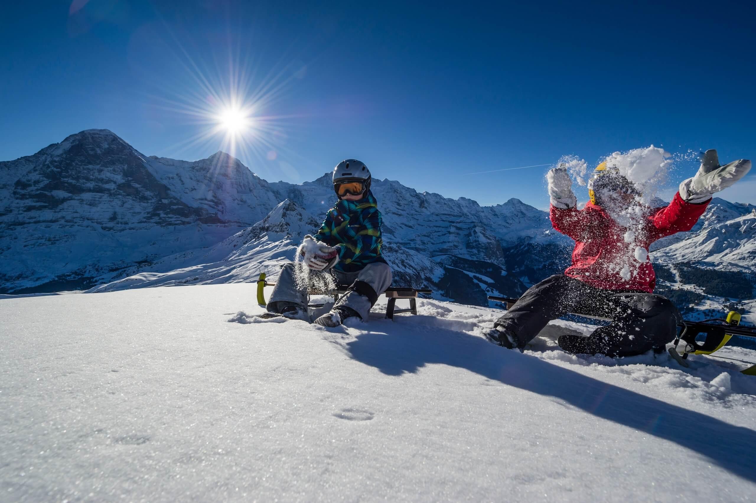 maennlichen-schlitteln-sonnenschein-winter-panorama