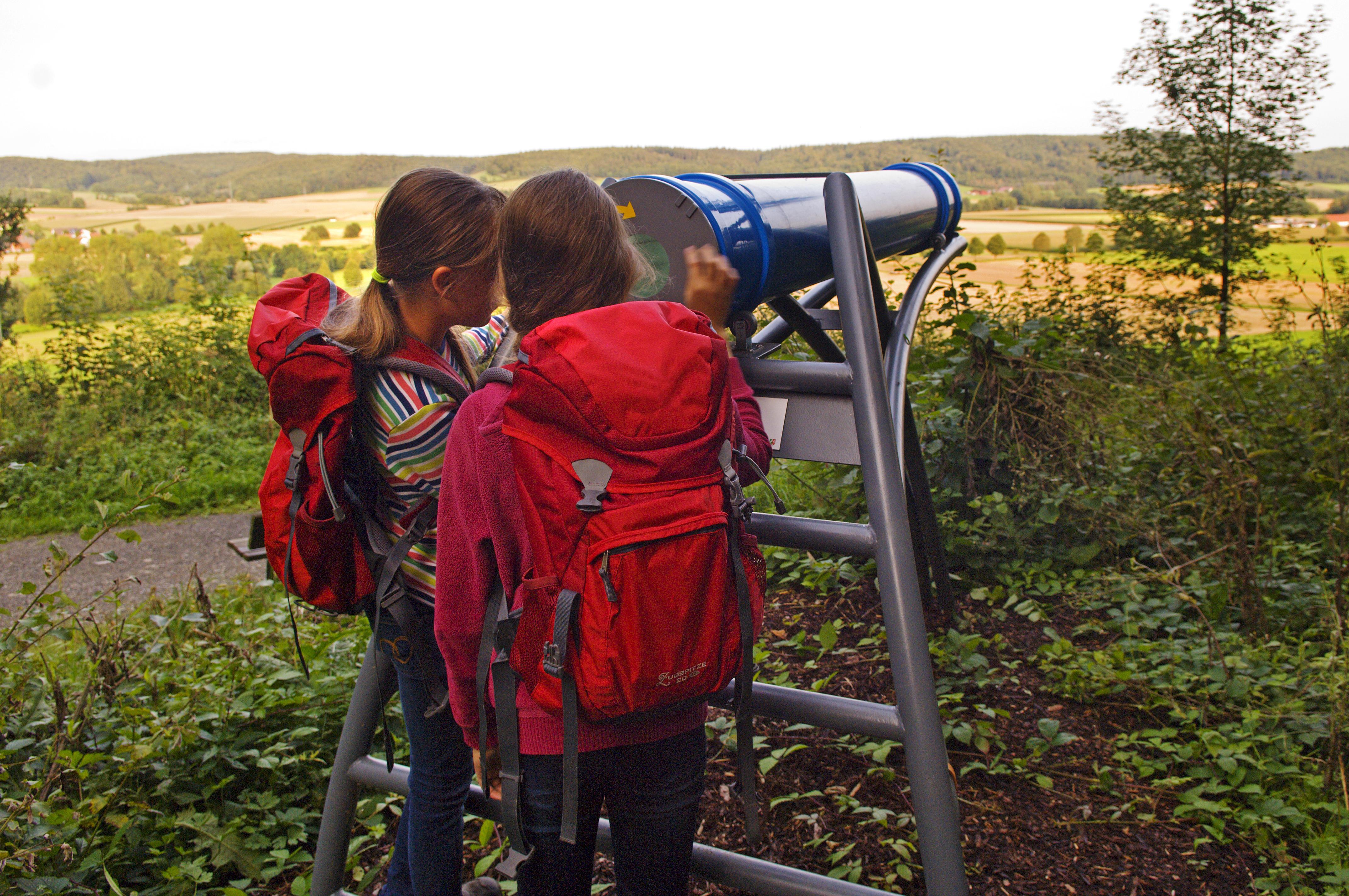 Mädchen mit Rucksäcken schauen durch das Sphäriskop