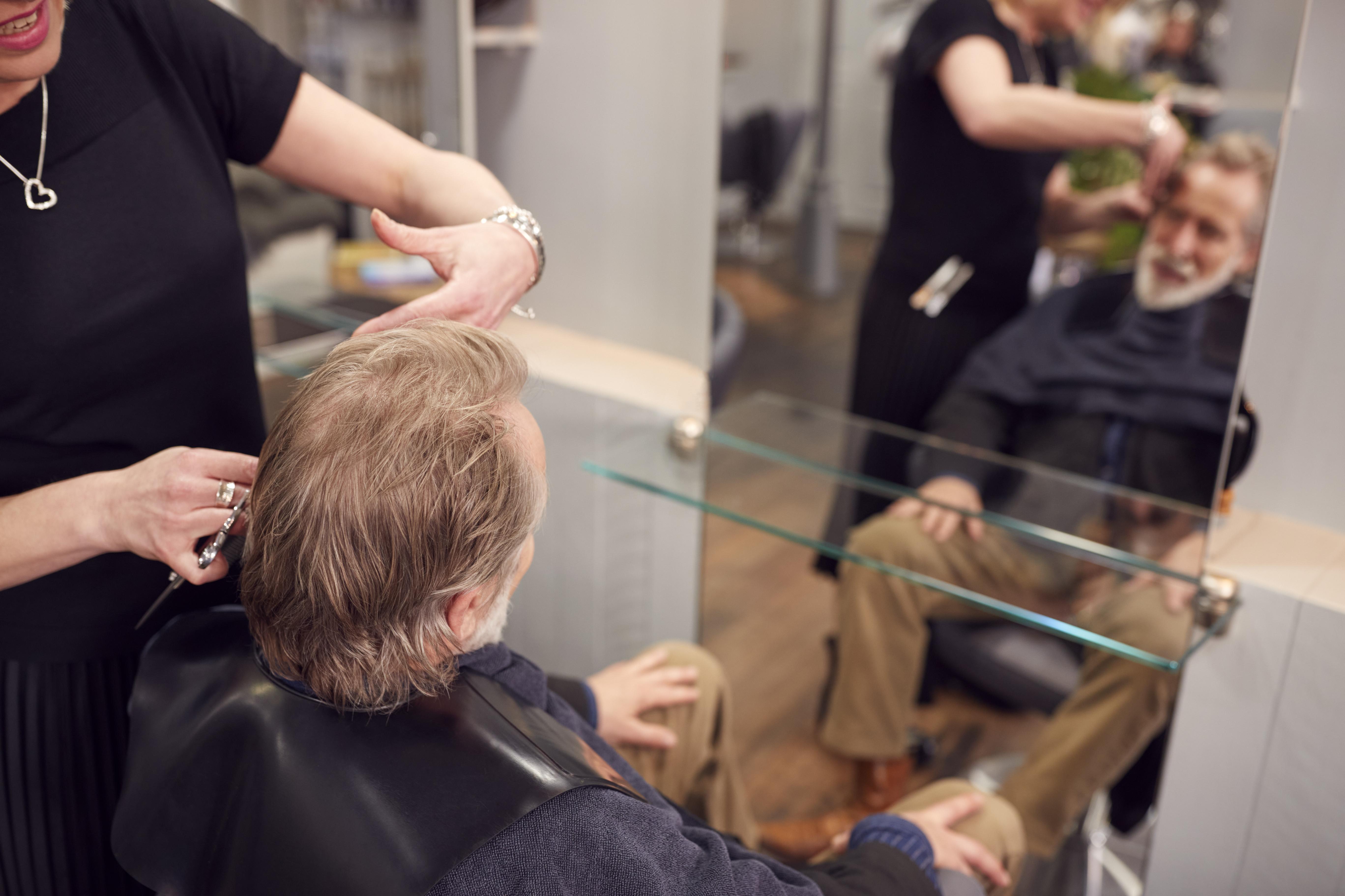 Senior Man Having Hair Cut By Female Stylist In Hairdressing Salon