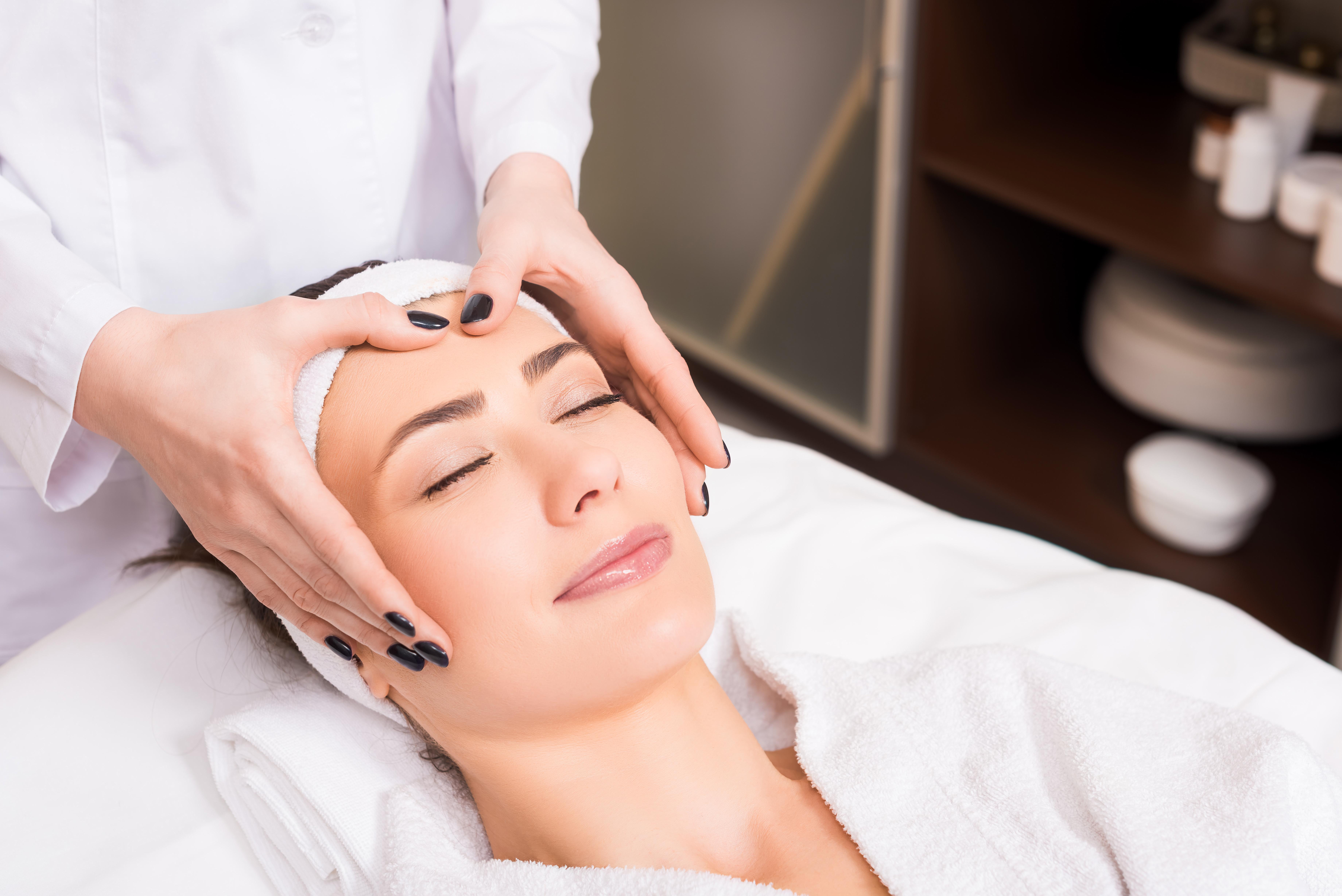 beautician doing manual massage on woman face at beauty salon