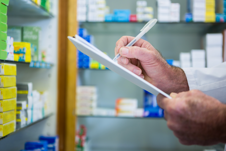 Pharmacist writing on clipboard in pharmacy