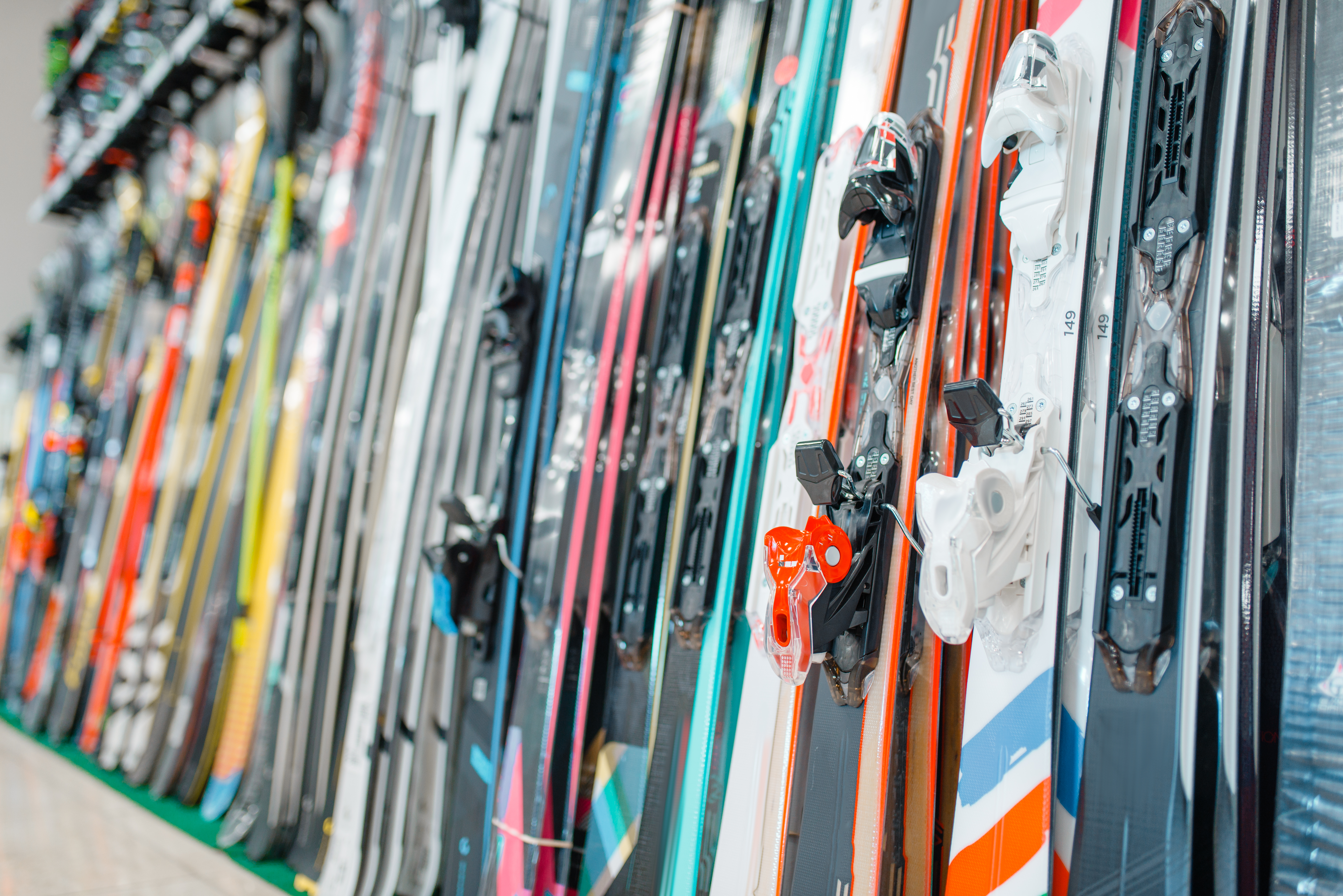 Rows of skis in sports shop, closeup, nobody. Winter extreme, active leisure, showcase with equipment