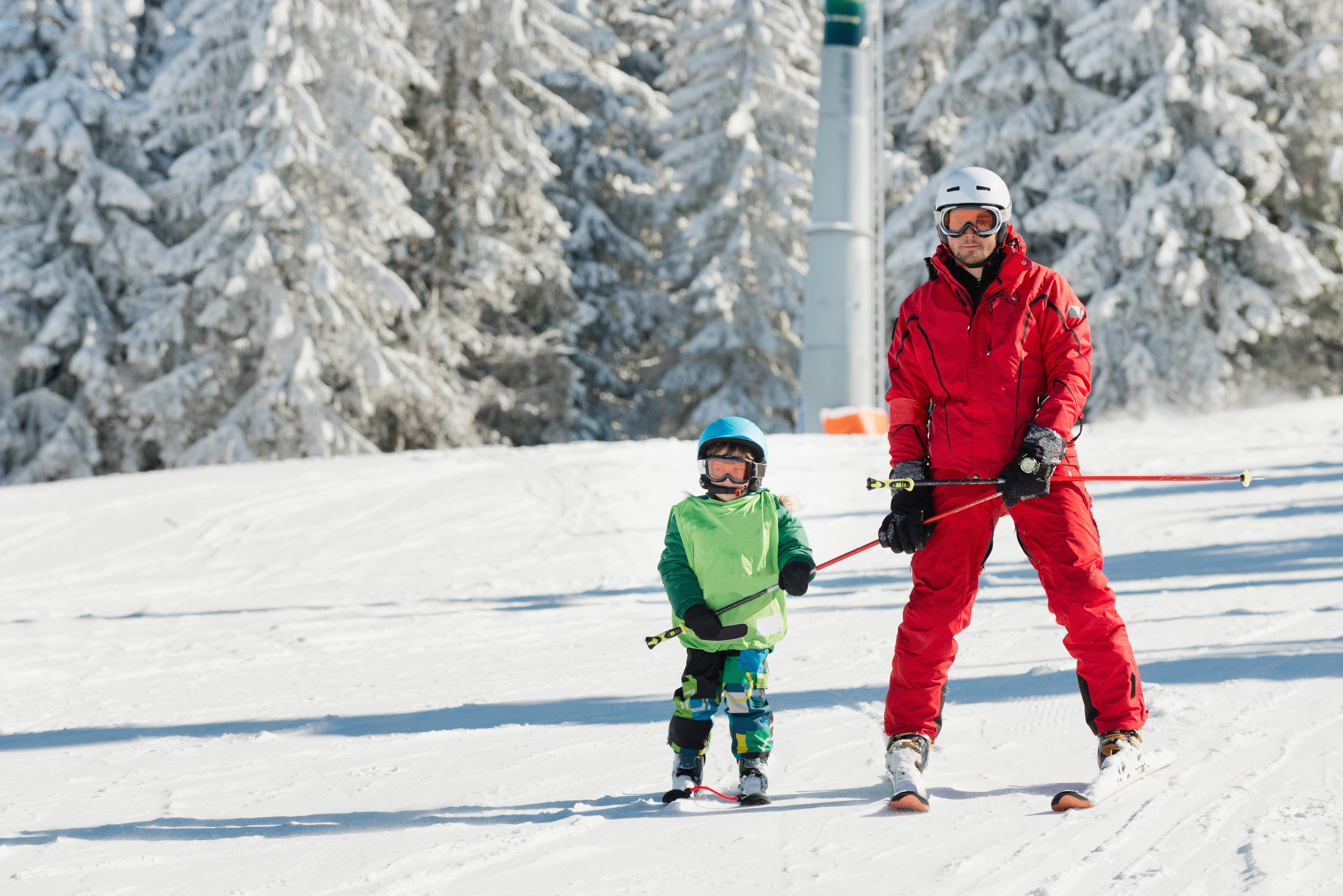 Ski instructor learning little boy skiing