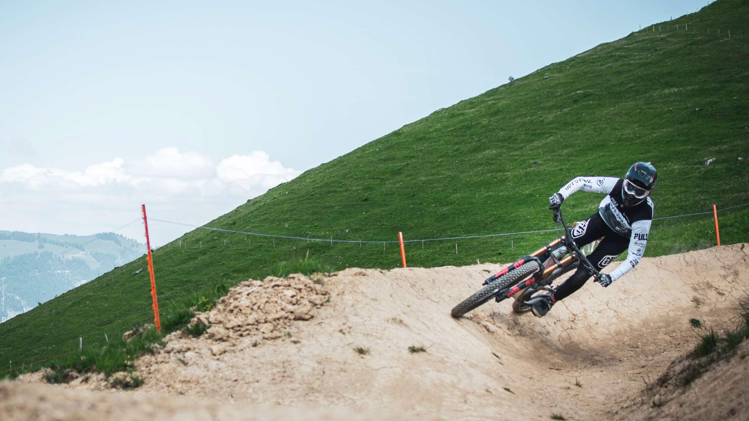 downhill-bikepark-wiriehorn-biker-auf-talfahrt-wiese-kurve.jpg