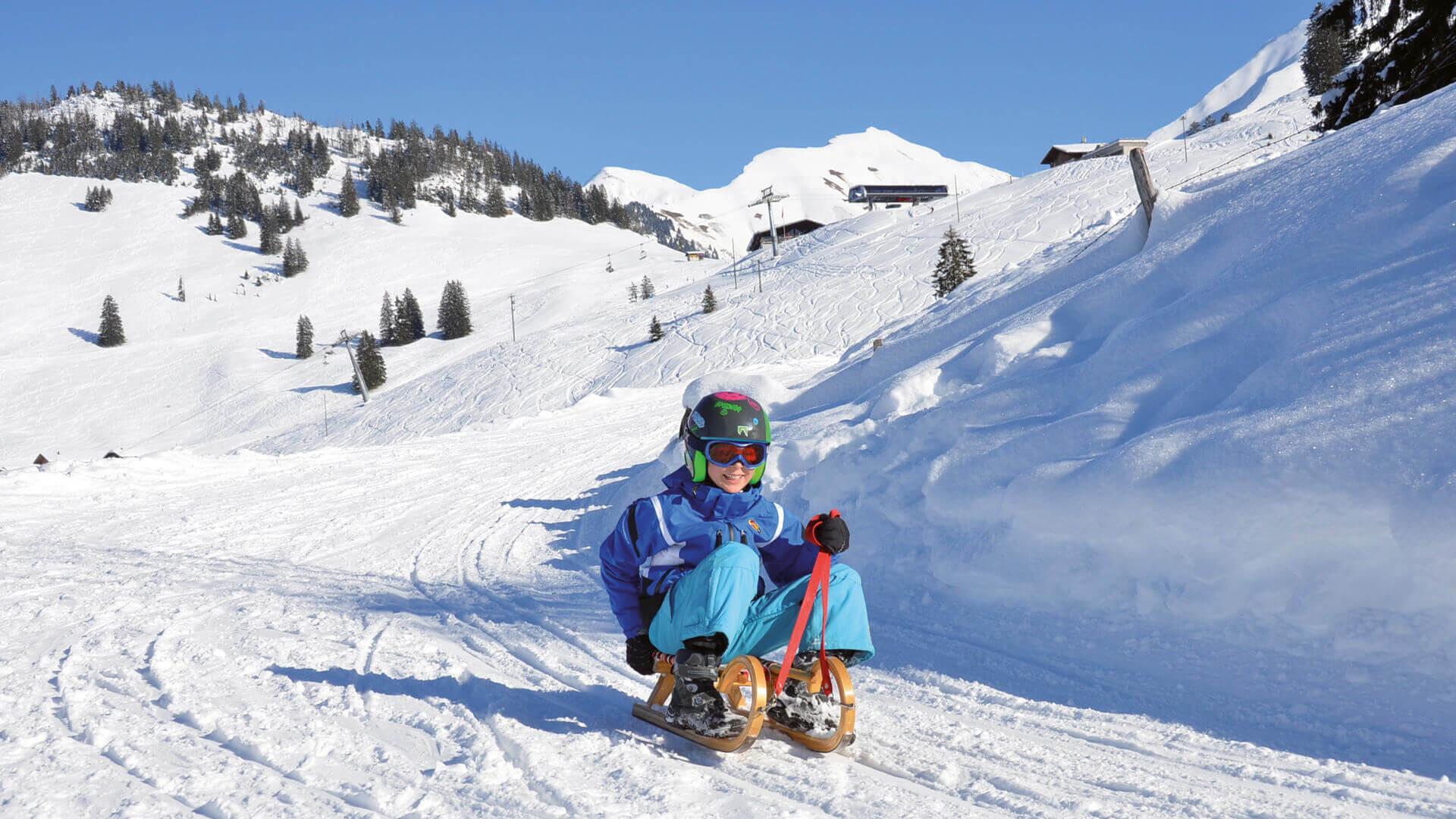 wiriehorn-schlitteln-kinder-himmel-blau-winteraktivitaet